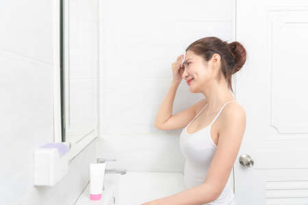 Beautiful Asian Woman applying cosmetic cream reflection in the mirror. Stockfoto
