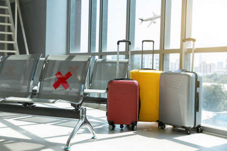 Traveling luggage in airport terminal and passenger plane flying over sky.