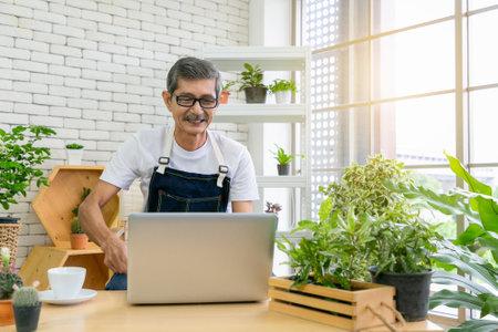 Senior man gardener working with camera presents houseplants during online live stream. 版權商用圖片