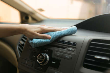 Close up worker hand cleaning console with microfiber cloth blue.