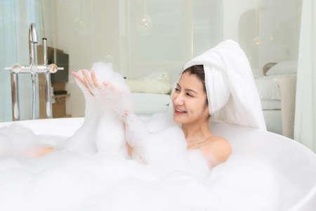 Happy asian woman bathes with white foam in a bathtub fun emotions. 版權商用圖片