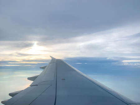 Wing of an airplane flying above in the evening