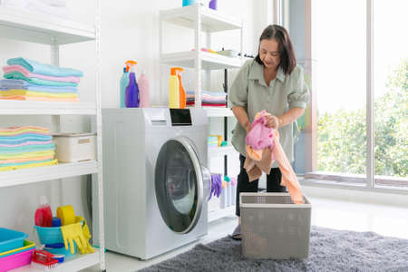 Close-up senoir woman housewife sitting with smiling and smelling white clean towel from washing machine in laundry room. 版權商用圖片