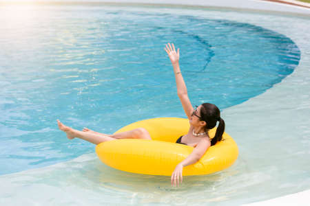 Beautiful asian woman with glass of summer cocktail on inflatable ring at pool, above view