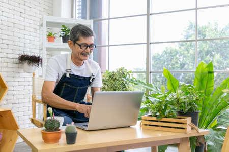 Senior man gardener using computer laptop watching movie at home with coffee.
