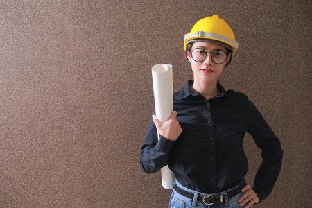 Business Asia woman engineer developer holding blueprint working Confident.