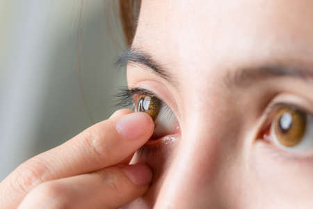 Close-up shot of young woman wearing or remove contact lens.