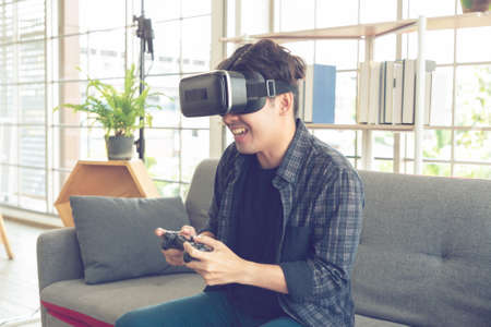 Happy young man with virtual reality headset or 3d glasses with controller gamepad playing video game at home.