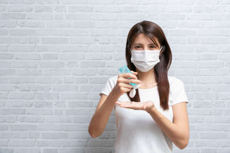 Asian woman in medical protective mask applying an antibacterial antiseptic hand gel for hands.