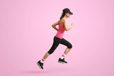 Sporty woman runner in silhouette on pink background. Side view. Sport and healthy lifestyle