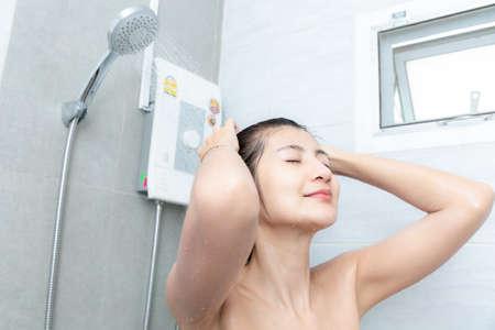 Beautiful asian young woman taking shower in bathroom.