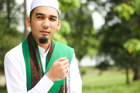 Smiling Muslim Man holding Tasbih in closeup shot