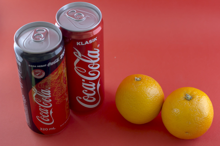 KAJANG, MALAYSIA - JANUARY 1, 2017: Closeup shot of Coca Cola Classic Tin Can and Coca Cola Zero on Red Background with Orange Lemon Editorial