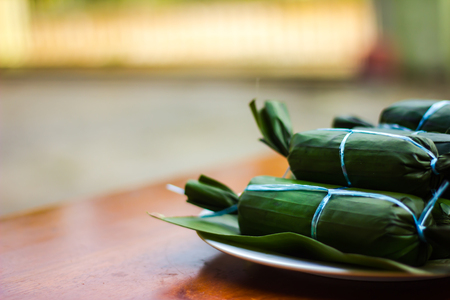Closeup shot of Ketupat Daun Pisang on wooden table in blur background . Malaysian cuisine Stock Photo - 103359515