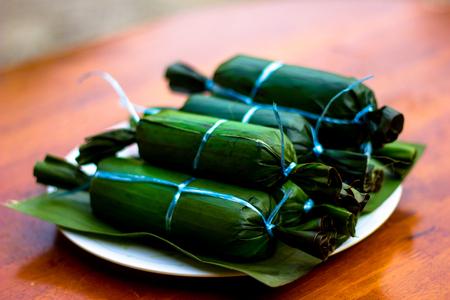 Closeup shot of Ketupat Daun Pisang on wooden table in blur background . Malaysian cuisine Stock Photo