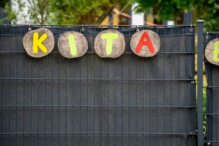 A black kindergarten fence with the abbreviation KITA in colorful letters on it.