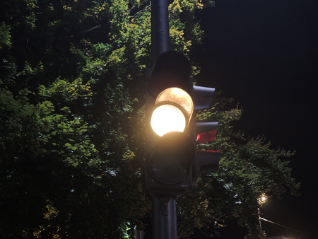 maybe: Traffic light at night-time showing yellow Stock Photo