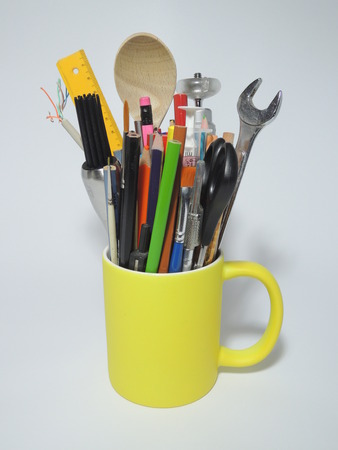 originative: Coffee cup filled with color pencils, workshop tools, kitchen tools, brushes, etc. The image illustrates a multi-talented person or a innovative person spanning multiple disciplines indicated by the broad range of tools.