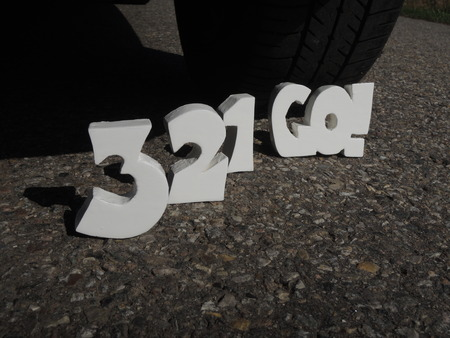 commence: 3D letters counting down 3-2-1-go! behind car. Stock Photo