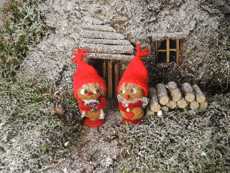 Gnomes in front of their cosy home in the forest. Can for instance be used as a christmas card