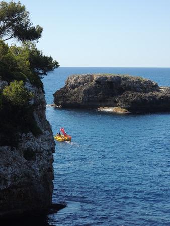 ambitious: Paddleboat on ambitious voyage near Cala dOr, Mallorca, Spain