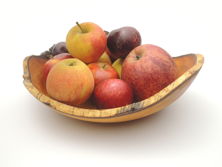 Wooden bowl with freshly picked home-grown Danish apples. Apple names are Ingrid Marie, Elstar, and Hosteiner Cox.
