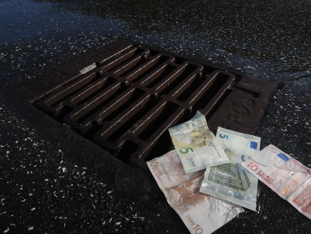 Euro bank notes going down the drain. A symbol of crisis, failure, loss, deficit, bad performance, etc.