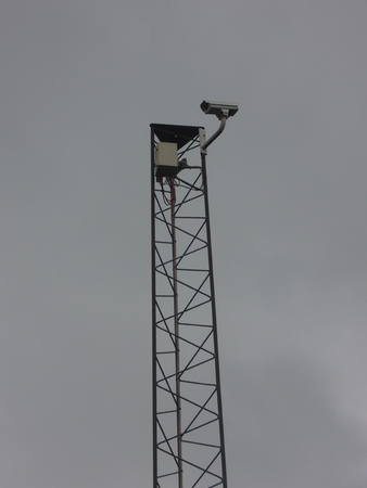 Surveillance cameras with dark clouds behind. For illustraing the problems with exceessive surveillance.