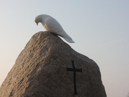 espiritu santo: Espíritu Santo sheparding un alma al cielo. La parte superior de una lápida danesa típica en granito en bruto con la cruz y la paloma del Espíritu Santo en la parte superior de la lápida