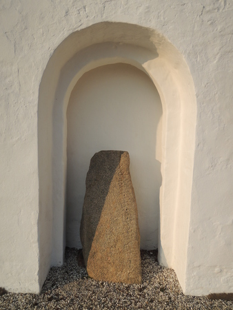 heathen: Viking runestone with runes placed in a arch outside a rural Danish church. Interesting placement since it marks the change of religion from the heathen viking religion to christianity. Stock Photo