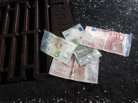 tough luck: Euro bank notes going down the drain. A symbol of crisis, failure, loss, deficit, bad performance, etc.