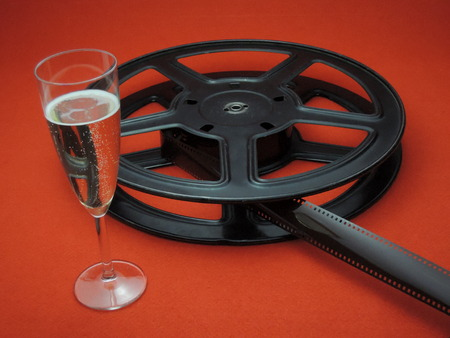Film reel and sparkling Champange on red carpet Stock Photo