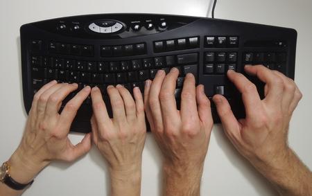 """De activiteit 'pair programming """"in extreme programmering en Scrum geïllustreerd door twee paar handen op het toetsenbord. Stockfoto"""