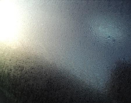 Waterdruppeltjes op een venster met zonlicht reflectie Stockfoto