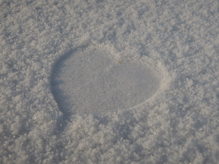 lost love: Lost love illustrated by the imprint of a heart in the snow