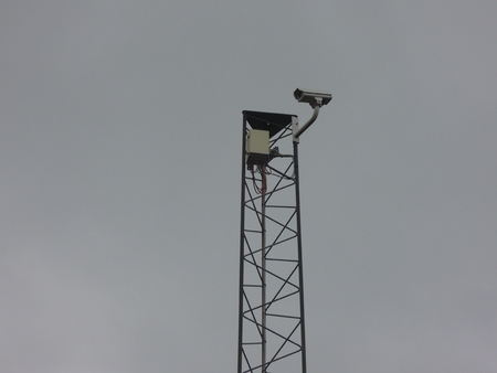 insecurity: Surveillance cameras with dark clouds behind. For illustraing the problems with exceessive surveillance.