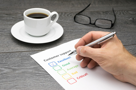 excellent service: Customer support center offering excellent service. Customer filling out survey form while having a coffee