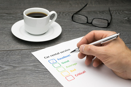 excellent service: Car rental service offering excellent service. Customer filling out survey form while having a coffee