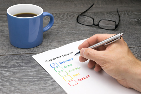 filling out: Customer service center offering excellent service. Customer filling out survey form while having a coffee