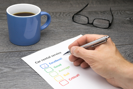 filling out: Car rental service offering excellent service. Customer filling out survey form while having a coffee