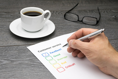 exemplary: Customer service center offering excellent service. Customer filling out survey form while having a coffee