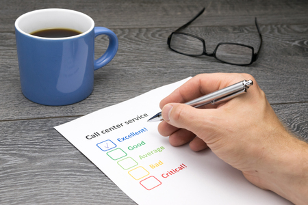 exemplary: Call center offering excellent service. Customer filling out survey form while having a coffee