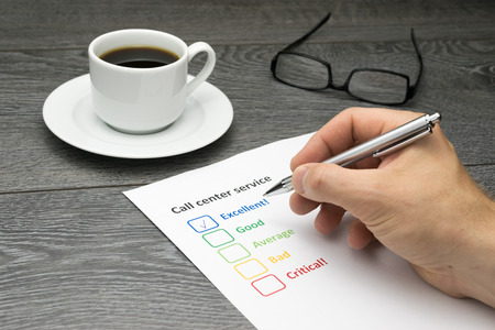 filling out: Call center offering excellent service. Customer filling out survey form while having a coffee