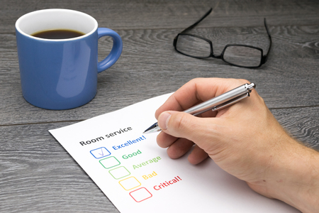 filling out: Hotel offering excellent room service. Customer filling out survey form while having a coffee