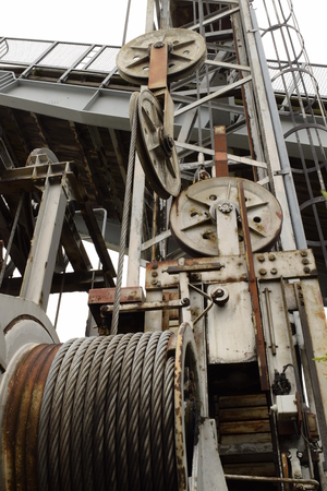 lowering: Old worn lifting system for a ferry slip with steel cables and wheels for raising and lowering the bridge.