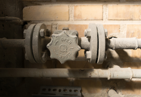 chalky: Old dusty and rusty open close valve and pipes on yellow brick wall.