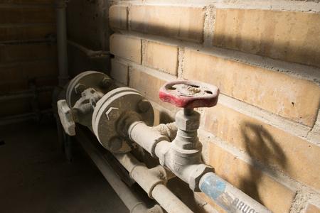 Alte staubige rote Ventil und Rohrleitungen auf gelbem Ziegelmauer. Standard-Bild - 60665172