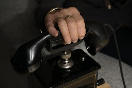 Grandma anticipating a call on the old black antique telephone Standard-Bild