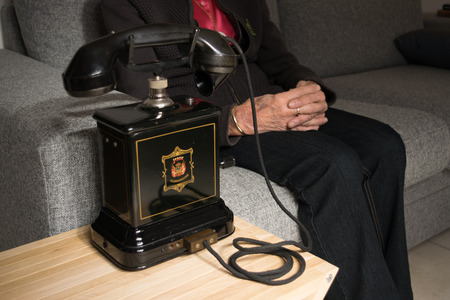Grandma anticipating a call on the old black antique telephone Imagens