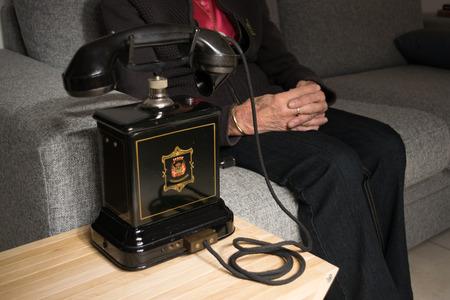 telefono antico: Grandma anticipating a call on the old black antique telephone Archivio Fotografico